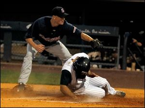 Gwinnett pitcher Joe Bisenius is late on the tag as Toledo's Mike Cervenak scores on a wild pitch.