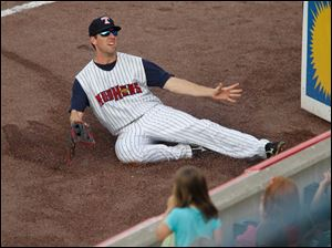 Right fielder Danny Dorn slides into the stands on an attempted catch of an out-of-reach ball.