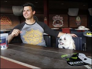 Bowling Green resident Alek Walker sits with his dog Beamer at a bar inside Fifth Third Field in Toledo, Ohio.