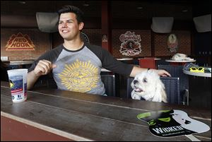Bowling Green resident Alek Walker sits with his dog Beamer at a bar inside Fifth Third Field.