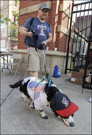 Matt Rose walks through the entrance to the stadium with his dog Duke, an English springer spaniel. Duke was named after a Pittsburgh Pirates' pitcher.