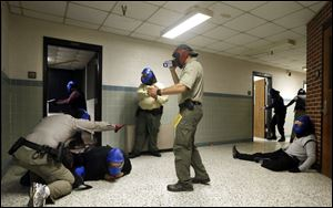 FBI instructor Mike Sotka, center, films local police officers as they participate in an active shooter drill in a college classroom building in Salisbury, Md., as part of an FBI program on Aug. 13.