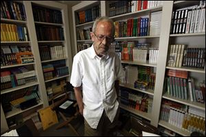 Author Elmore Leonard, 86, stands in his Bloomfield Township, Mich., home. Leonard, a former adman who later in life became one of America's foremost crime writers, has died. He was 87. His researcher says he passed away Tuesday morning, Aug. 20, 2013 from complications from a stroke.