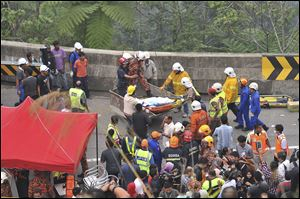 Malaysian emergency services personnel rescue a passenger by a crane after a passenger bus carrying tourists and local residents fell into a ravine near the Genting Highlands, about an hour's drive from Kuala Lumpur, Malaysia early today.
