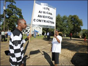 Mario Wallace, 42, left, and Tyrone Farrow, 54, both of Toledo, display a sign advocating the hiring of African-American contractors during a news conference.