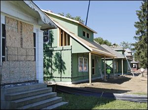 Two new homes, part of the Legacy Homes project, are under construction next to a vacant house in the 300 block of West Delaware Avenue in Toledo.