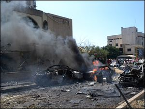 Burned and destroyed cars are seen at the entrance of a mosque, left, which was attacked by a car bomb, in the northern city of Tripoli, Lebanon today.