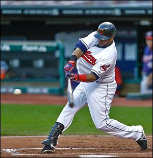 The Indians' Carlos Santana hits an RBI-single off the Twins' Samuel Deduno in the first inning to score Michael Bourn.