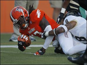 Bowling Green's Travis Greene picks up a first down as he is tackled by Idaho's Gary Walker in September, 2012.