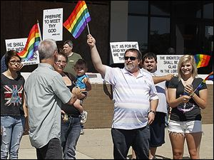 The Owens Community College Gay Straight Alliance marches in the annual Toledo Pride parade on Saturday. In its fourth year, the parade has become a major downtown event.