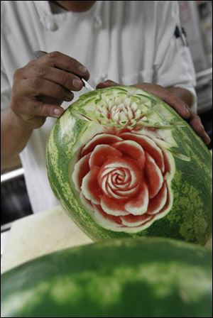 Food artist Tien Pham carves a flower into a watermelon while working in the Sylvania Country Club kitchen.