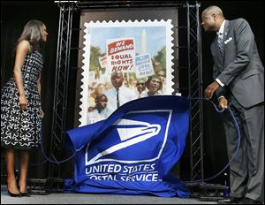 Actor  Gabrielle Union and Deputy Postmaster General Ronald Stroman unveil the U.S. Postal Service stamp commemorating the march's 50th anniversary.