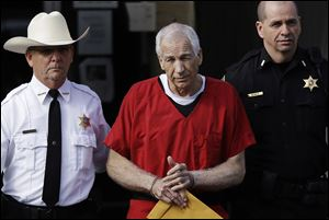 Former Penn State University assistant football coach Jerry Sandusky, center, is taken from the Centre County Courthouse in October, 2012.