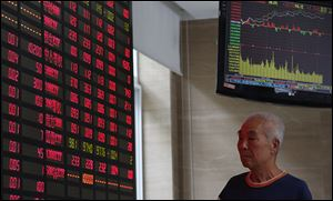 An investor looks at a stock prices monitor at a private securities company today in Shanghai, China. Asian stock markets mostly rose today after expectations for an imminent phasing out of the Federal Reserve's monetary stimulus program began to fade.