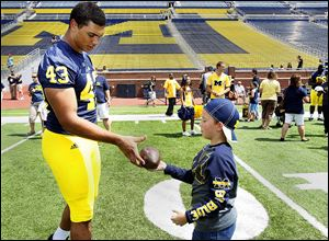 Whitmer graduate and Michigan defensive end Chris Wormley signs an autograph for  Camden Dings, 7, of Toledo, during the recent Fan Day. He is likely to see plenty of playing time this season.