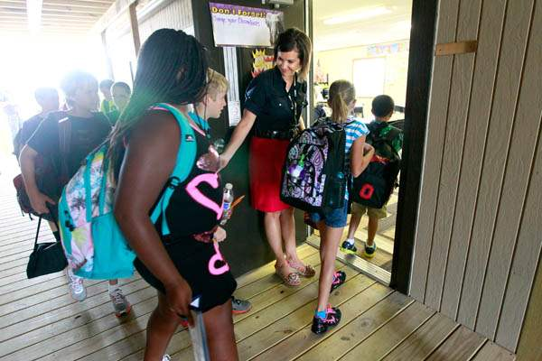 Fifth-grade-teacher-Jennifer-Krueger-left-welcomes-her-students-with-a-smile