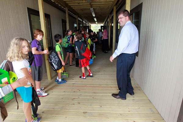 Scott-Best-principal-right-greets-fifth-grade-students-as-they-head-into-class