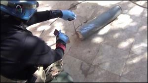 In this image taken from amateur video posted online, appearing to show a presumed U.N. staff member measuring and photographing a canister in the suburb of Moadamiyeh in Damascus, Syria, Monday.