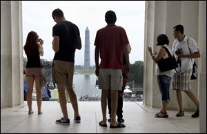Tourists look out from the Lincoln Memorial to the Washington Monument in Washington Tuesday. President Obama, who will speak, was 2 years old and growin