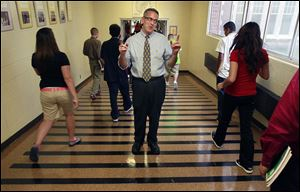 Principal Dave Yenrick directs students through the hallway after lunch on the first day of school at Waite High School. He's been principal there for 19 years and has a long family history at the school.