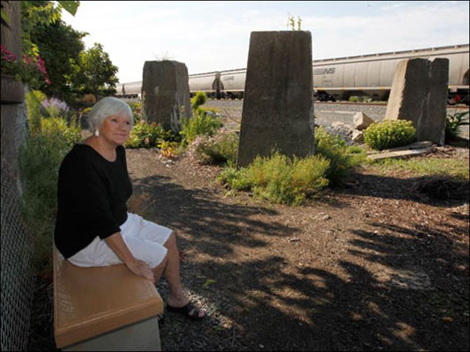 FEA wiartraintracks16p Bev Newell watches a passing train on Oakdale at White streets in Toledo. She planted a garden there and loves to watch the trains go by. She is sitting on a bench she made for the garden.
