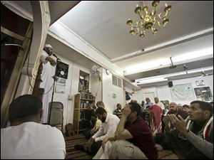 Dr. Muhamad Albar, far left, speaks to a congregation during Jumu'ah prayer service at the Islamic Society of Bay Ridge mosque on Friday in the Brooklyn borough of New York.