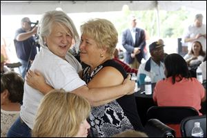 Jeep retirees Irene Preuss, left, and Sophia Anponiuk hug at the Toledo-Lucas County Port Authority's ceremony to mark the development of the Overland Industrial Park on the former Jeep plant site.