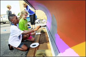 Crim Elementary school students Mozelle Ofori-Atta, left, 9, and Bethany Yoast, 10, right, work on the plows while art teacher Noreen Overholt, back right, explains to Jordan Brenner, left, 9, how to paint the blade that they designed. Painted snow plows fro