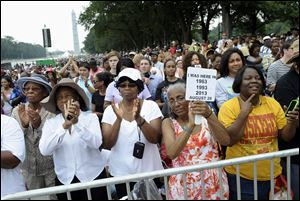 Three women who attended previous Marches on Washington, from left, Armanda Hawkins of Memphis, Vera Moore of Washington, and Betty Waller Gray of Richmond, Va., with sign, listen to speakers.