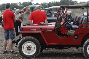 Keith Buckley of Stow, center, talks with Rogan Murdock of Perrysburg, right, near a few classic Willy's Jeeps after the port authority's ceremony to mark the development of the future Overland Industrial Park.