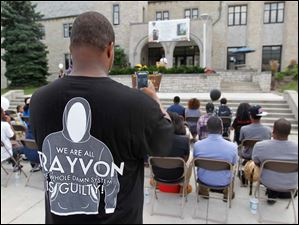 Kenneth Brown, president of Student African American Brotherhood, takes a photo during a rally at the University of Toledo Student Union for the anniversary of the March on Washington and to reflect on the recent trial over the death of Trayvon Martin.