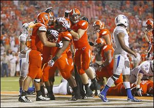 Bowling Green's William Houston, center, is congratulated by teammates after scoring a touchdown in the fourth quarter against Tulsa at Doyt Perry Stadium in Bowling Green. The Falcons blew open the close game in the second half.