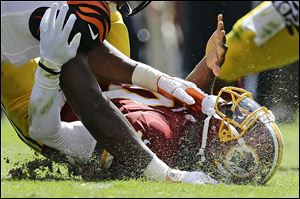 Washington Redskins quarterback Robert Griffin III hits the turf after being sacked in this 2012 file photo. NFL executives want to change the culture of the league _ and all of football _ to reduce head injuries.