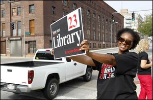 Pauline Kynard holds up a sign for a 2012 library levy campaign during a kickoff event in front of Fifth Third Field in September of that year.
