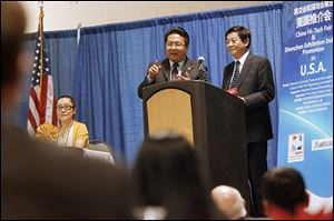 Simon Guo, left, chairman of Five Lakes Global Group USA, translates for Gao Guohui, deputy secretary general of the China Hi-Tech Fair, who was addressing businessmen and politicians at SeaGate Convention Centre in downtown Toledo.