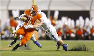 Bowling Green quarterback Matt Johnson scrambles for a first down before being tackled by University of Tulsa players Trenton Martin, left, and Mitchell Osborne.