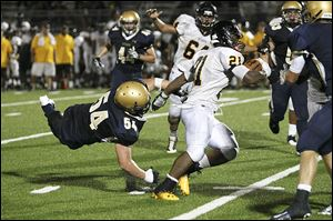 St. John's Jesuit senior Geno DeMarco misses the tackle as Cleveland Heights player Marcus Bagley runs toward a 275-yard game on 29 carries, including touchdown runs of 2, 1, 8, and 5 yards.