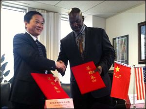 Toledo Mayor Mike Bell and Gao Guohui, deputy secretary-general of the Shenzhen Municipal government, shake hands after signing a cooperative agreement between the two cities.