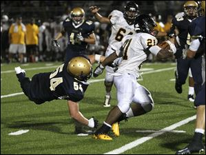 St. John's Jesuit senior Geno DeMarco misses the tackle as Cleveland Heights player Marcus Bagley runs the ball.