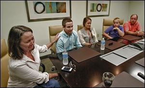 The Fudacz family — from left, mom Ellen, Paul, Jr., Sarah, Joseph, and dad Paul, Sr. — discuss the painful events of the last year in the law offices of James E. Arnold & Associates in Columbus.