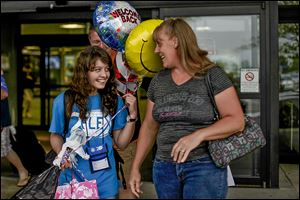 Bakhtiniso Kamaloua, 15, an exchange student from Tajikistan, and her host, Yulinda Cousino of Gibsonburg, can't conceal happiness after Bakhtiniso's arrival at Toledo Express Airport on Aug. 22. Bakhtiniso started classes Monday at Gibsonburg High and has joined the cross country team.