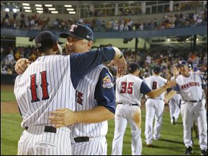 Toledo Mud Hens manager Phil Nevin gets a hug from player Argenis Diaz (11) after the Hens defeat the Columbus Clippers at Fifth Third Field, Saturday, August 31, 2013.