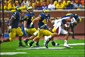 Central Michigan's Winslow Chapman is tackled by Michigan's Channing Stribling as he is chased by a group of Wolverines. Michigan had four sacks in  the game.