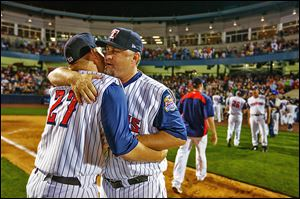 Toledo Mud Hens manager Phil Nevin gets a hug from player Kenny Faulk (27) after the Hens defeat teh Columbus Clippers at Fifth Third Field, Saturday, August 31, 2013.