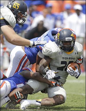Toledo running back David Fluellen, right, is tackled after a short gain by Florida defensive back Brian Poole, lower left, and linebacker Michael Taylor, center, in the first half.