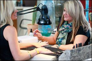 Nail stylist Cortnee Minkowski, right, creates nail art on Amanda Wrozek's nails at Future Wave in Oregon.