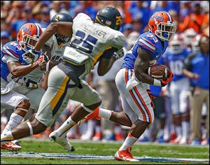 Florida's Mack Brown runs past Toledo's Chaz Whittaker. Brown filled in for starter Matt Jones and finished with 112 yards rushing.
