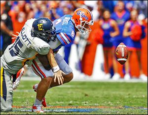 Florida QB Jeff Driskel fumbles as he is hit by Toledo defensive end Jayrone Elliott. The Gators fumbled twice and lost one ball.