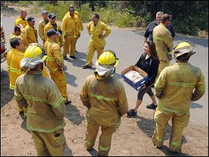 Modesto's Jessy Boonstra, from Ripon Immanuel Christian Reformed Church, carries a box of home baked cookies she brought along with Ripon Fire Chief and San Joaquin County Operational Area Coordinator Dennis Bitters, on a surprise visit to a strike team of San Joaquin County firefighters working along Forest Service road 31 behind Long Barn off of Hwy 108 Wednesday afternoon.
