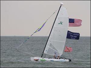 A sailor flies the colors on a small Hobie.